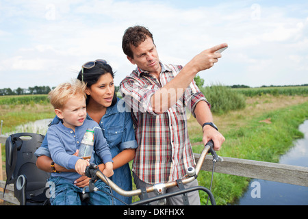 Family with bicycle, having drink, pointing - Stock Photo