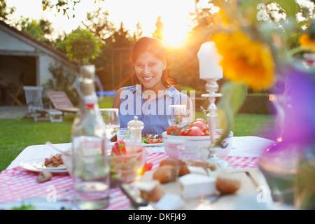 Woman having dinner in garden - Stock Photo