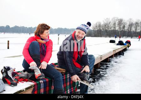 Couple sitting on pier putting on ice skates - Stock Photo