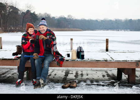 Couple sitting on pier having hot drink - Stock Photo