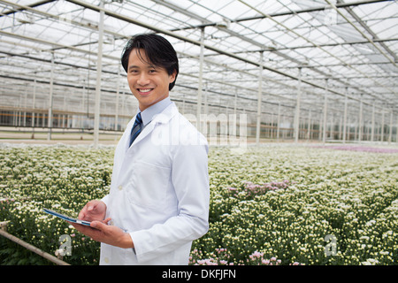 Man standing in front of rows of plants growing in greenhouse, holding tablet - Stock Photo