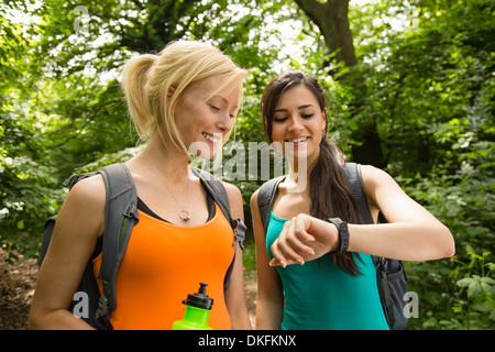 Women out walking in forest, checking the time - Stock Photo