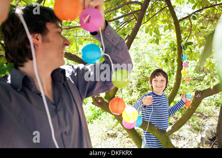 Father and son putting fairy lights in tree - Stock Photo