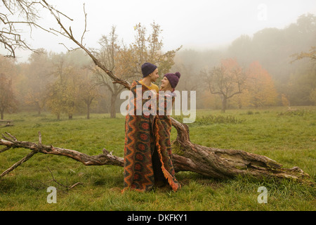 Young couple wrapped in blanket in misty park - Stock Photo