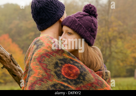 Close up of young couple wrapped in blanket in misty park - Stock Photo