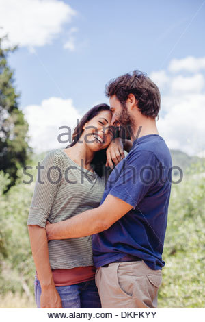 Happy mid adult couple hugging outdoors - Stock Photo