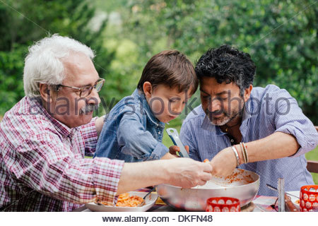Three generations of male family enjoying a meal together - Stock Photo