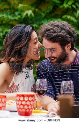 Couple whispering at outdoor meal - Stock Photo