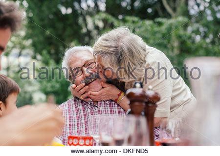 Senior woman kissing husband on cheek - Stock Photo