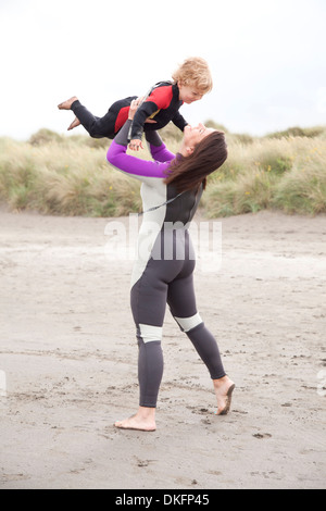Mother lifting son on beach - Stock Photo