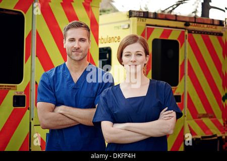 Portrait of two emergency medical technicians next to ambulance - Stock Photo