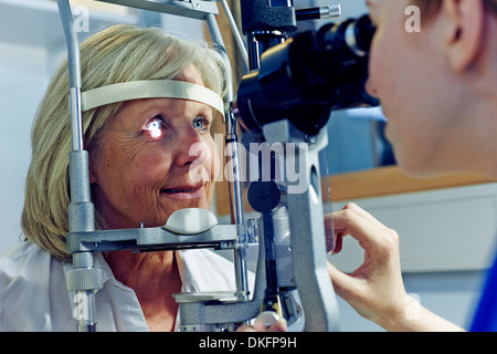 Female patient having eye tested in hospital - Stock Photo