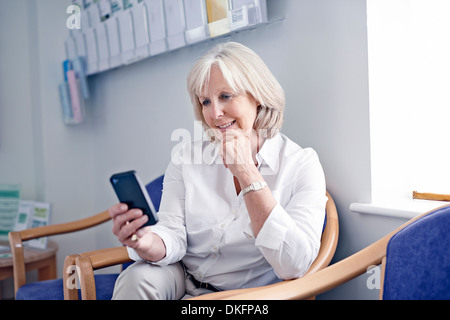 Mature female patient looking at mobile phone in hospital waiting room - Stock Photo