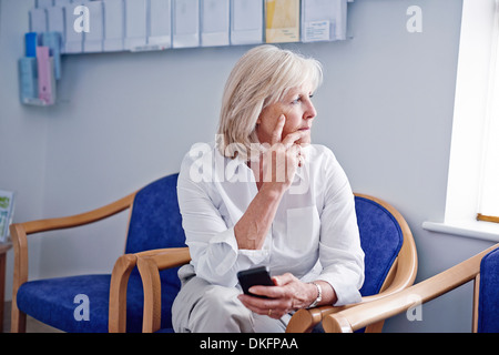 Mature female patient with mobile phone in hospital waiting room - Stock Photo