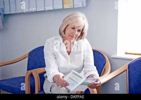 Mature female patient reading leaflet in hospital waiting room - Stock Photo