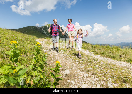 Parents and daughter walking on dirt track, Tyrol, Austria - Stock Photo