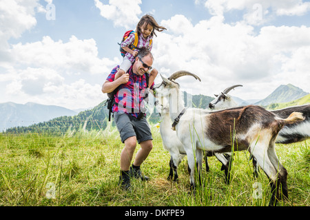 Father and daughter with goats, Tyrol, Austria - Stock Photo
