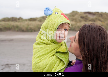 Portrait of mother holding son wrapped in a towel - Stock Photo