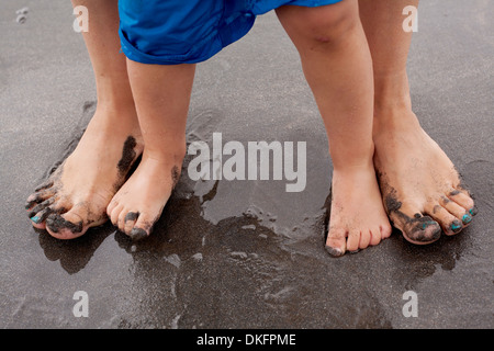 Mother and son standing on wet sand