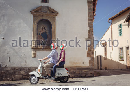 Couple looking at church painting from moped, Florence, Italy - Stock Photo
