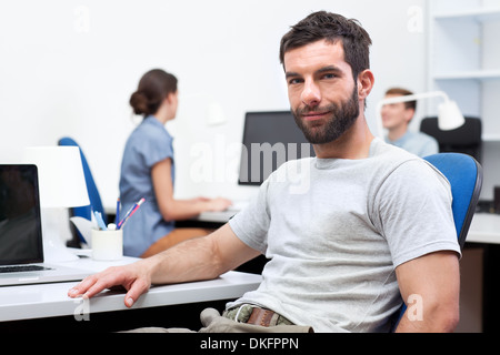 Mid adult man sitting at desk in office - Stock Photo