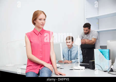 Young woman wearing pink blouse in office - Stock Photo