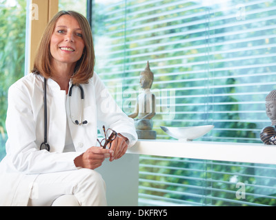 Doctor sitting at desk in office - Stock Photo