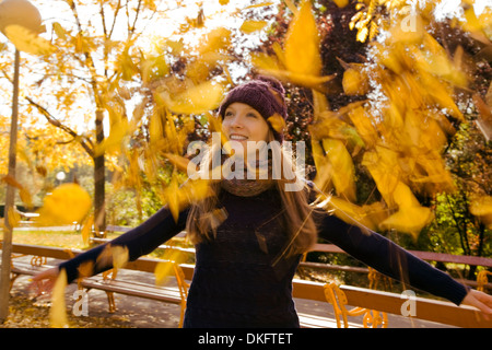 Young woman throwing up autumn leaves in park - Stock Photo