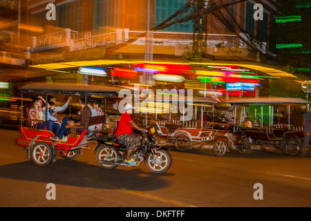 Motion blur image of a tuk-tuk at night in the capital city of Phnom Penh, Cambodia, Indochina, Southeast Asia, - Stock Photo