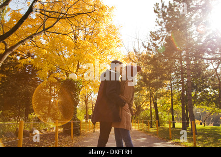 Young couple kissing in autumn park, Vienna, Austria - Stock Photo