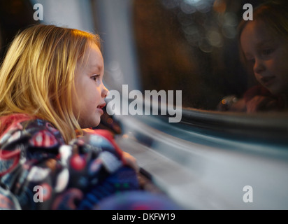 Girl looking out of a bus window during a journey at night - Stock Photo