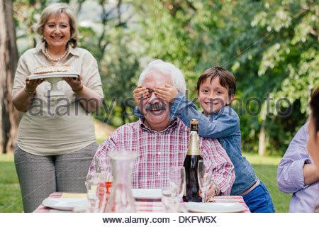 Senior man being surprised with birthday cake - Stock Photo