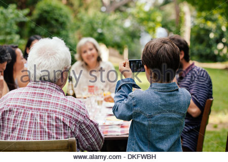 Boy photographing family at outdoor meal - Stock Photo