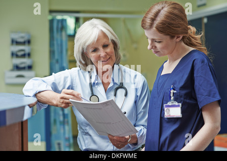 Two female doctors looking at medical record - Stock Photo