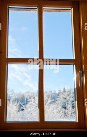 Sitting in a warm room looking out of the window at the first snow this winter early on a frosty morning - Stock Photo