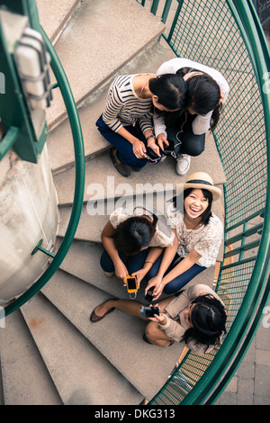 Five young women sitting on steps looking at smartphones - Stock Photo