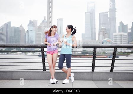 Female friends on bridge in Shanghai, China - Stock Photo