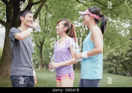 Jogger friends taking a break in park - Stock Photo
