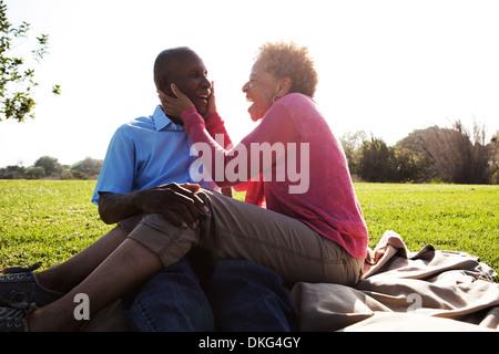 Portrait of senior couple sitting in park - Stock Photo