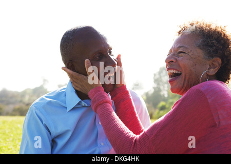 Portrait of senior couple in park, woman touching man's face - Stock Photo