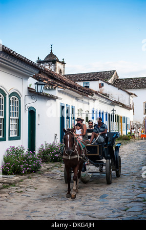 Horse cart with tourists riding through the town of Paraty, Rio de Janeiro, Brazil, South America - Stock Photo