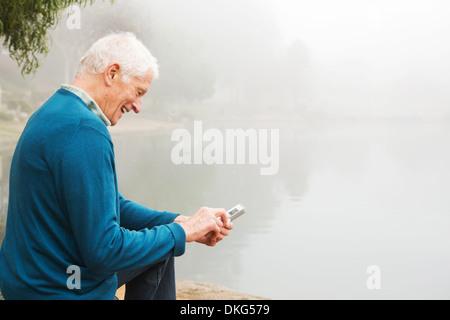 Senior man smiling at text on mobile phone - Stock Photo