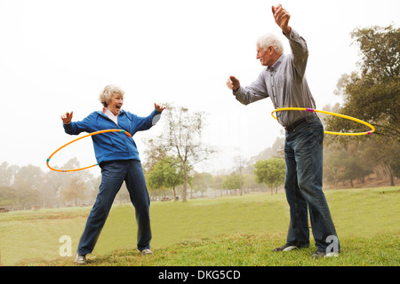 Husband and wife playing hula hoop in the park - Stock Photo