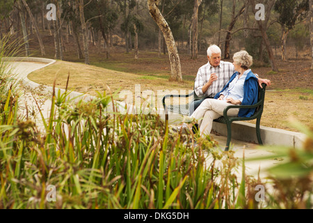 Husband and wife chatting lovingly on park bench - Stock Photo