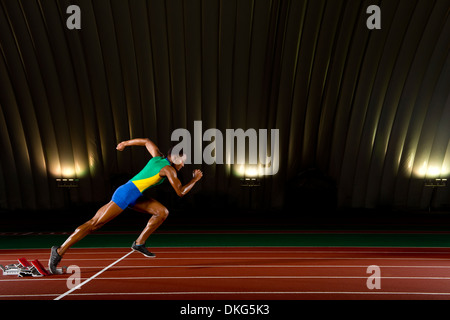 Young woman sprinting from starting blocks in stadium - Stock Photo