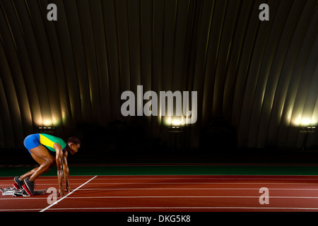 Young woman sprinting on starting blocks in stadium - Stock Photo