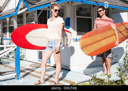 Couple on patio carrying surfboards, Breezy Point, Queens, New York, USA - Stock Photo