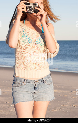 Young woman holding camera on beach, Breezy Point, Queens, New York, USA - Stock Photo