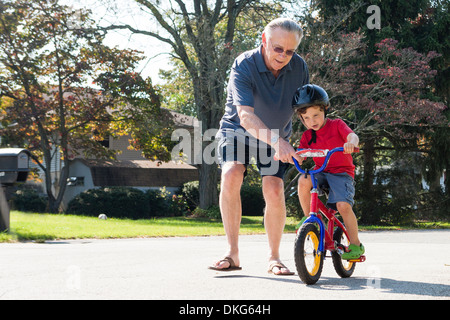 Grandfather encouraging young boy to ride bicycle - Stock Photo