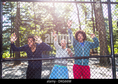 Young men by wire fence in park - Stock Photo